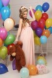 Femme enceinte avec de longs cheveux blonds dans la robe élégante, avec beaucoup de ballons à air colorés image libre de droits