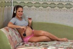 Femme enceinte avec des écouteurs Photographie stock