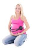 Femme enceinte avec des écouteurs sur son estomac Images stock