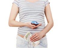 Femme enceinte avec des billets de banque de cinq cents hryvnias et d'une tirelire Photo libre de droits
