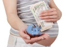 Femme enceinte avec des billets de banque de cinq cents hryvnias et d'une tirelire Image libre de droits