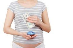 Femme enceinte avec des dollars et une tirelire dans les mains Image stock