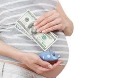 Femme enceinte avec des dollars et une tirelire dans les mains Photo libre de droits