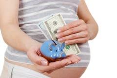 Femme enceinte avec des dollars et une tirelire dans les mains Images stock