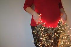 Femme enceinte avec des lumières de Noël Image stock
