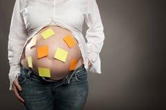 Femme enceinte avec des notes de post-it Image libre de droits