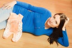 Femme enceinte avec des vêtements pour le bébé à venir Images libres de droits