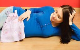 Femme enceinte avec des vêtements pour le bébé à venir Photos stock