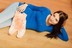 Femme enceinte avec des vêtements pour le bébé à venir Image libre de droits