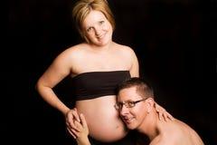 Femme enceinte avec l'écoute de mari Images stock