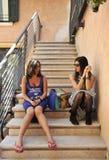 Femme enceinte avec l'amie s'asseyant sur les étapes dans un village italien Photographie stock libre de droits