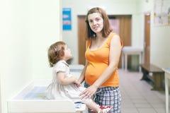 Femme enceinte avec l'enfant à la clinique Photographie stock
