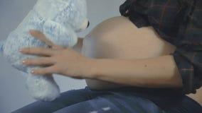 Femme enceinte avec l'enfant jugeant teddybear près de jouer de ventre clips vidéos