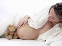Femme enceinte avec l'ours de nounours Photographie stock libre de droits