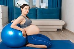 Femme enceinte avec la boule d'ajustement Photographie stock libre de droits