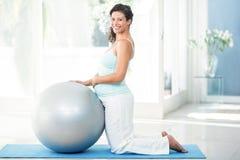 Femme enceinte avec la boule d'exercice kneeing sur le tapis photos libres de droits