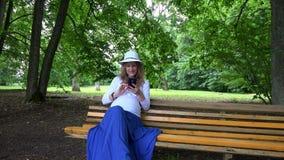 Femme enceinte avec la photo de selfie de prise de chapeau se reposant en parc sur le banc banque de vidéos