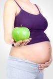 Femme enceinte avec la pomme verte à disposition Images stock