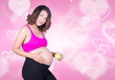 Femme enceinte avec la pomme verte sur le fond de coeur Image stock