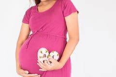 Femme enceinte avec le bébé de chaussures Photos stock
