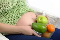 Femme enceinte avec le bol de fruits et légumes Photos stock