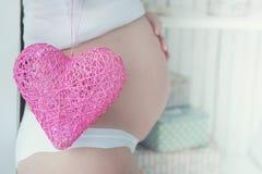 Femme enceinte avec le coeur rose simple sur sa bosse de bébé Images stock