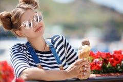 Femme enceinte avec le cornet de crème glacée près de l'océan photo libre de droits
