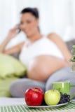 Femme enceinte avec le fruit sur la table Photo libre de droits