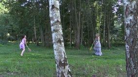 Femme enceinte avec le jeu de badminton de jeu de fille de fille en parc clips vidéos