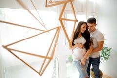 Femme enceinte avec le mari devant la fenêtre Photo libre de droits