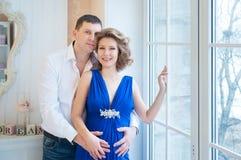Femme enceinte avec le mari Les couples s'approchent de la fenêtre Photographie stock libre de droits