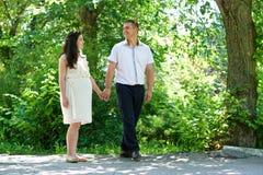 Femme enceinte avec le mari marchant pendant parc de ville, portrait de famille, la saison d'été, herbe verte et arbres Photos libres de droits