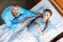 Femme enceinte avec le mari tenant des mains et regardant l'appareil-photo dans l'hôpital photo libre de droits