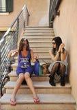 Femme enceinte avec le meilleur ami s'asseyant sur les étapes dans un village italien Photographie stock libre de droits