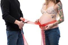 Femme enceinte avec le ruban rouge autour du ventre posant avec le mari Photographie stock