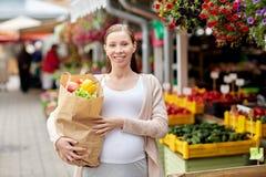 Femme enceinte avec le sac de la nourriture au marché en plein air Photos stock