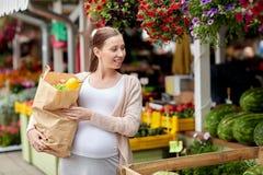 Femme enceinte avec le sac de la nourriture au marché en plein air Photographie stock