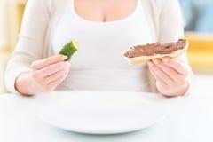 Femme enceinte avec le sandwich à conserves au vinaigre et à chocolat photographie stock