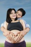 Femme enceinte avec le symbole d'amour Photo stock