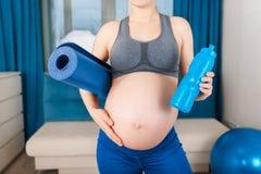 Femme enceinte avec avec le tapis de yoga Photos stock