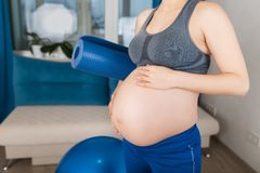 Femme enceinte avec le tapis de yoga Images libres de droits