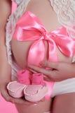 Femme enceinte avec le ventre de cadeau tenant le petit chausson du bébé dans sa main Photo stock