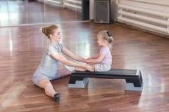 Femme enceinte avec sa fille faisant la gymnastique photo stock