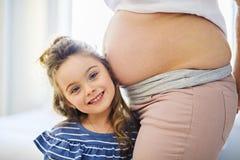 Femme enceinte avec sa fille sur la chambre à coucher ensemble photographie stock libre de droits