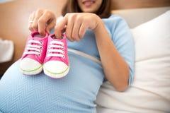 Femme enceinte avec une paire de chaussures de bébé roses d'espadrilles Photos stock
