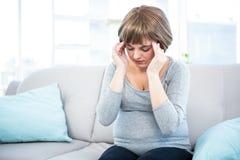 Femme enceinte ayant le mal de tête sur le divan Images stock