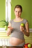 Femme enceinte choisissant entre les pillules et la pomme Images libres de droits