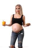 Femme enceinte choisissant entre un hamburger et un poivre Fin vers le haut Fond blanc Image stock