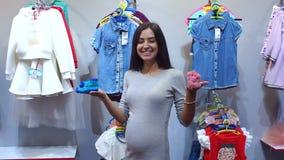 Femme enceinte choisissant l'habillement de bébé dans le bébé et la boutique de maternité banque de vidéos