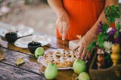 Femme enceinte coupant la tarte aux pommes faite maison Photographie stock